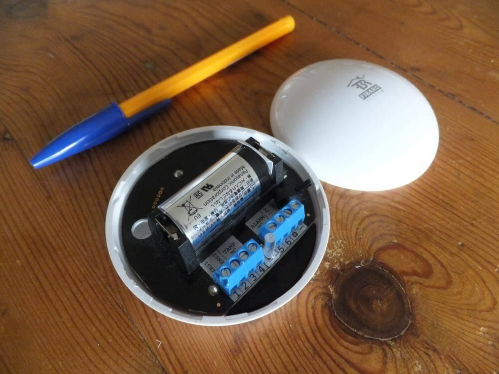 Le Flood Sensor FGFS-101 ouvert, au côté d'un simple stylo. Notez la compacité de l'appareil Fibaro !