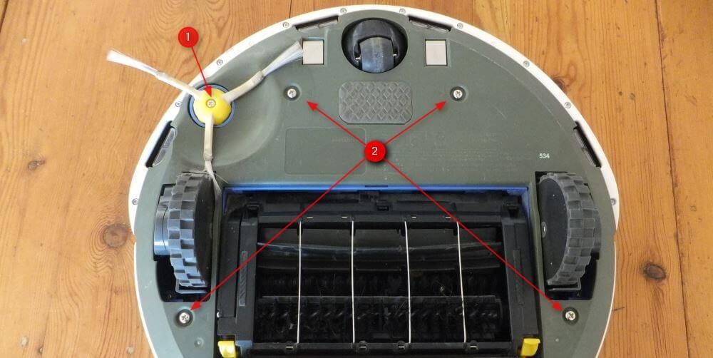 On commence par démonter la brosse latérale (1), avant de dévisser les 4 autres vis (2). Il n'y a plus qu'à retirer le capot.