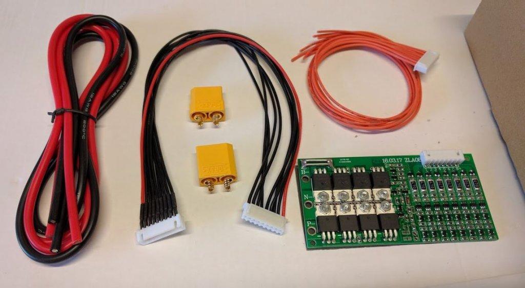 De gauche à droite : les câbles de puissance, un câble avec une borne JST-XH 8S femelle, 2 bornes XT90, le BMS et son câble JST-XH 7S associé.